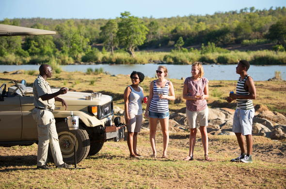 Guests enjoying drinks on a game drive in Kruger National Park.
